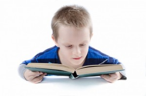 Boy in blue shirt reading a book